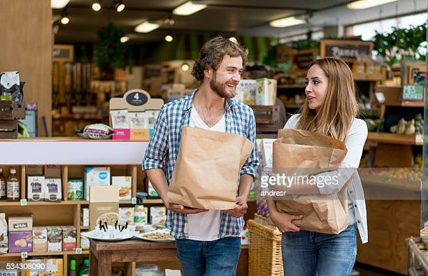 happy couple grocery shopping - organisch stock-fotos und bilder
