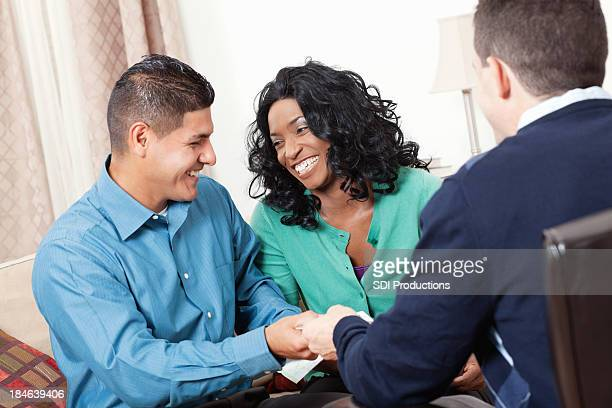 Happy couple handing over credit cards to financial counselor