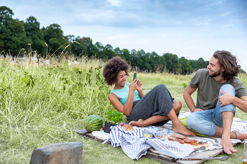 Happy couple having a barbecue and taking cell phone pictures in the nature - gettyimageskorea