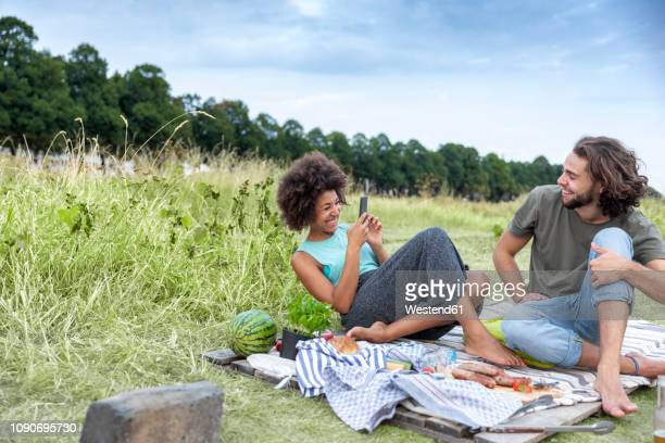 happy couple having a barbecue and taking cell phone pictures in the nature - picknick stock-fotos und bilder