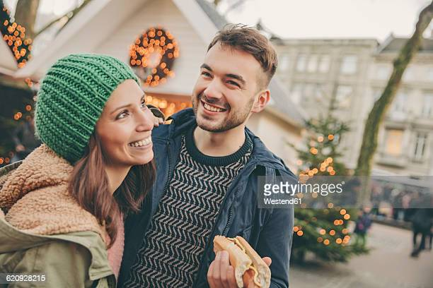 Happy couple having a snack on the Christmas Market