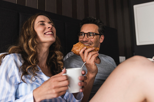 Happy couple having breakfast in bed at home - gettyimageskorea