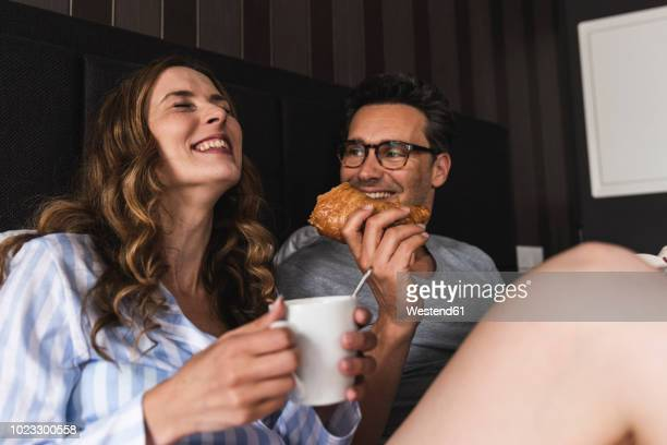 Happy couple having breakfast in bed at home