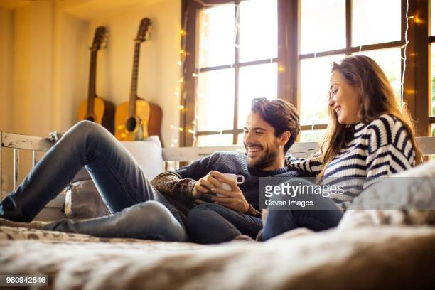 Happy couple having coffee while resting on alcove window seat at home