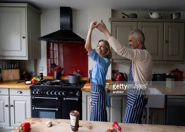 happy couple having fun dancing while cooking together - dancing stock pictures, royalty-free photos & images