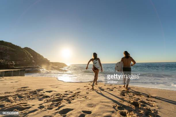 happy couple having fun surfing at the beach - beach stock pictures, royalty-free photos & images