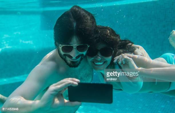 Happy couple having fun taking a selfie underwater