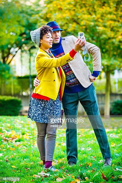 Happy couple having fun taking selfie with compact camera