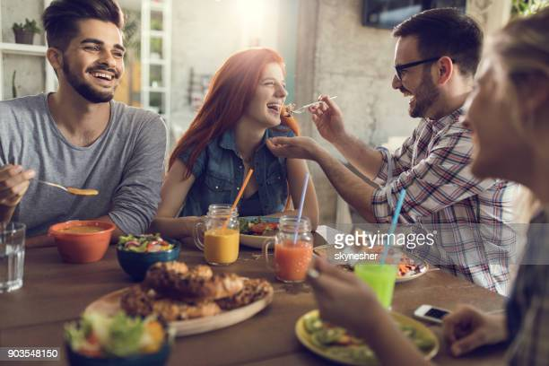 Happy couple having fun while eating lunch with their friends in a restaurant.