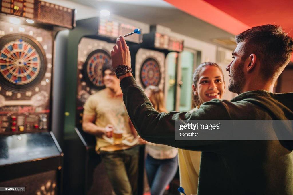 Happy couple having fun while playing darts in a pub. : Stock Photo