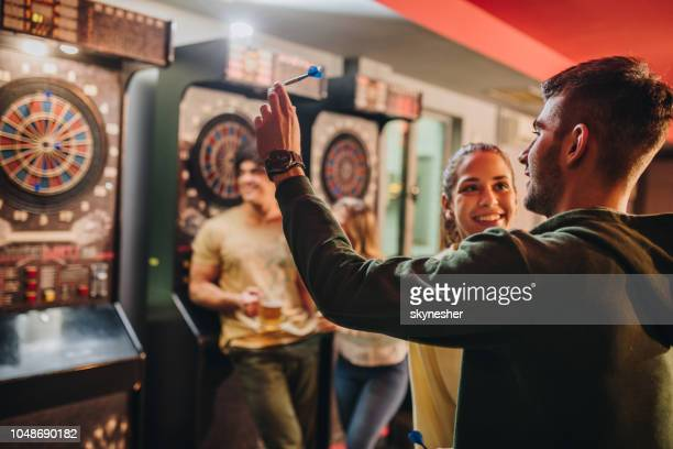 happy couple having fun while playing darts in a pub. - darts stock pictures, royalty-free photos & images