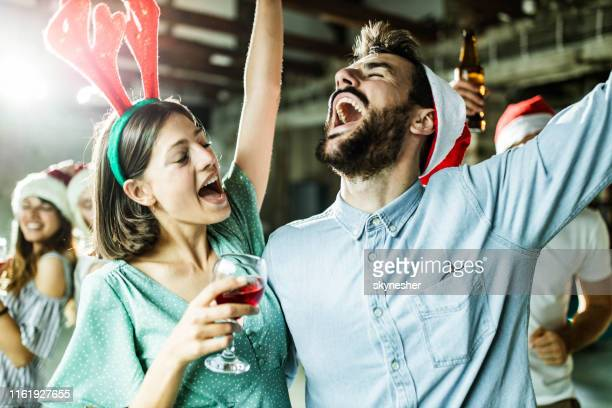 happy couple having fun while singing on christmas party. - party stock pictures, royalty-free photos & images