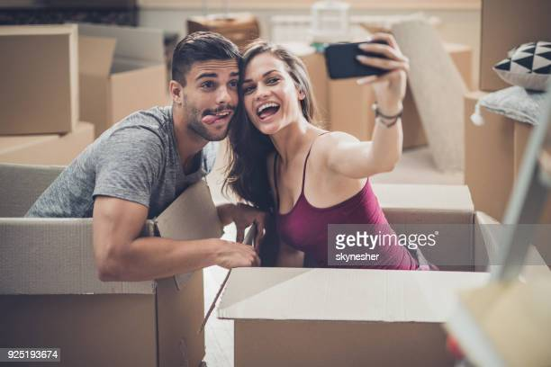 Happy couple having fun while taking a selfie at their new home.