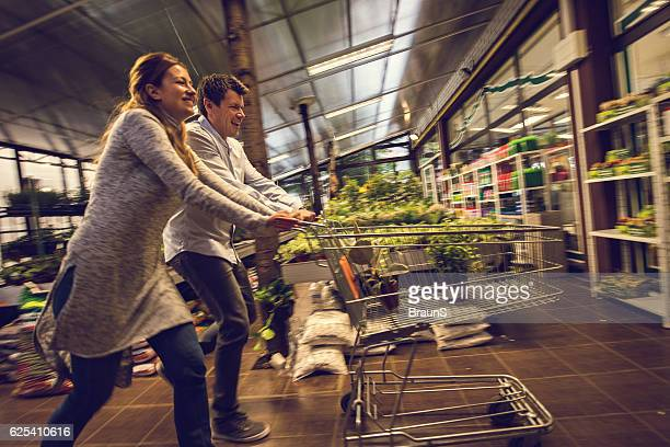 Happy couple having fun with shopping cart in garden house.