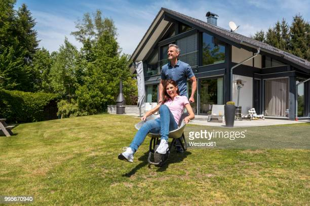 Happy couple having fun with wheelbarrow in garden of their home