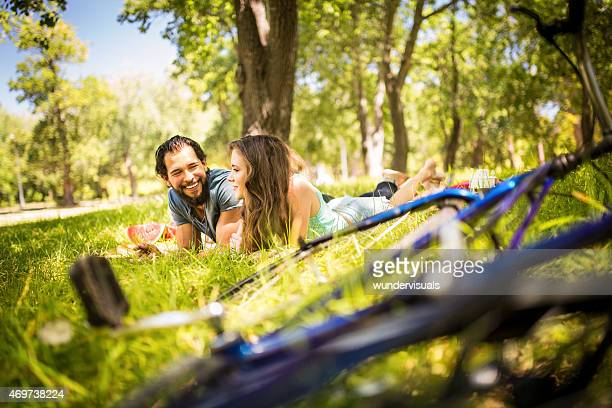 Happy couple having picnic with their bikes in foreground