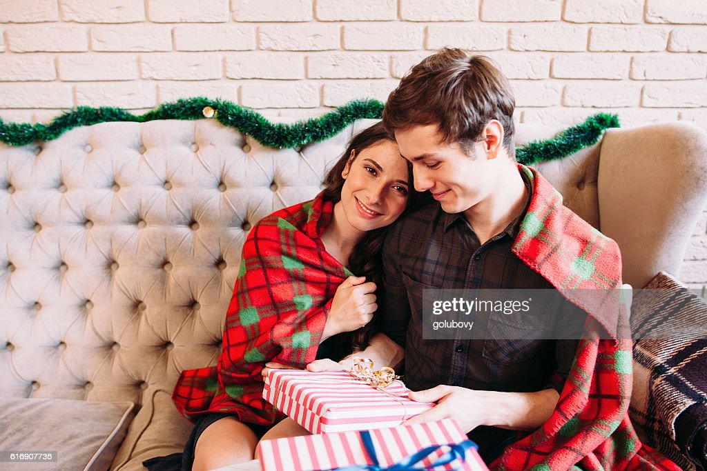Happy couple having rest near Christmas gifts : Stock Photo