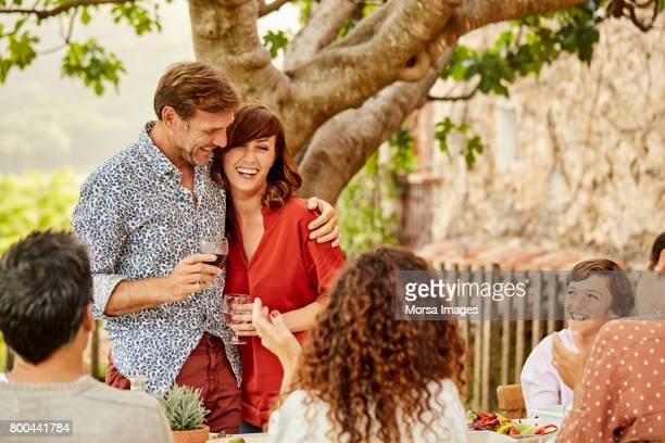 Happy couple having wine with family at lunch