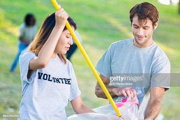 Happy couple help neighbors clean up park