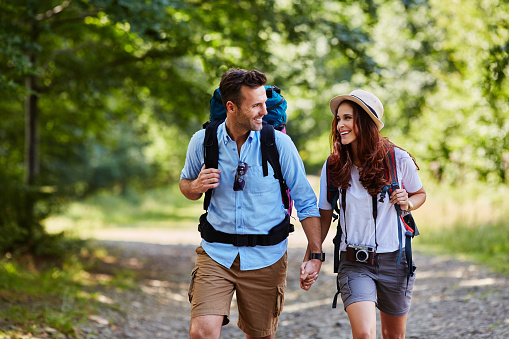 Happy couple hiking together in mountains with backpacks 943000932