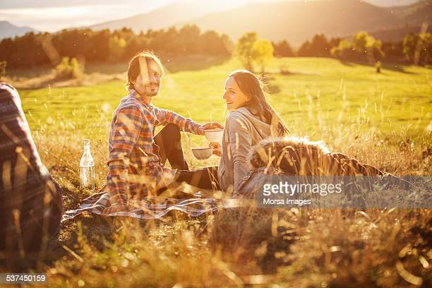 happy couple holding bowls on field - picknick stock-fotos und bilder