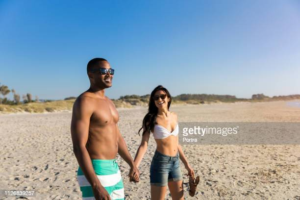 happy couple holding hands at beach - hot pants stock pictures, royalty-free photos & images