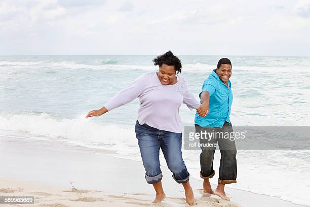 happy couple holding hands on beach - fat guy on beach stock pictures, royalty-free photos & images
