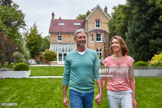 happy couple holding hands on field against house - in front of stock pictures, royalty-free photos & images