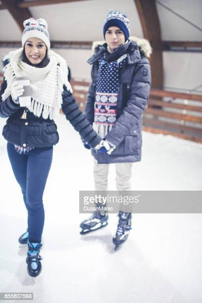 happy couple holding hands on skating rink - amateur stock pictures, royalty-free photos & images