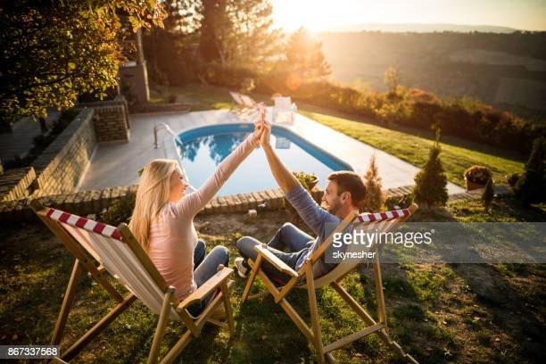 Happy couple holding hands while relaxing in deck chairs by the pool.
