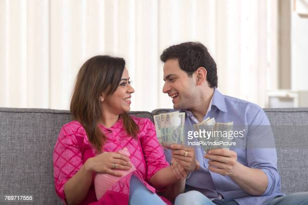 Happy couple holding indian currency and clay piggy bank