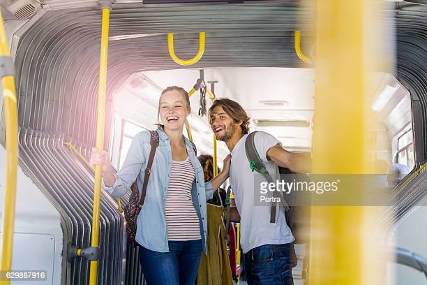 happy couple holding poles while standing in bus - foco técnica de imagem - fotografias e filmes do acervo
