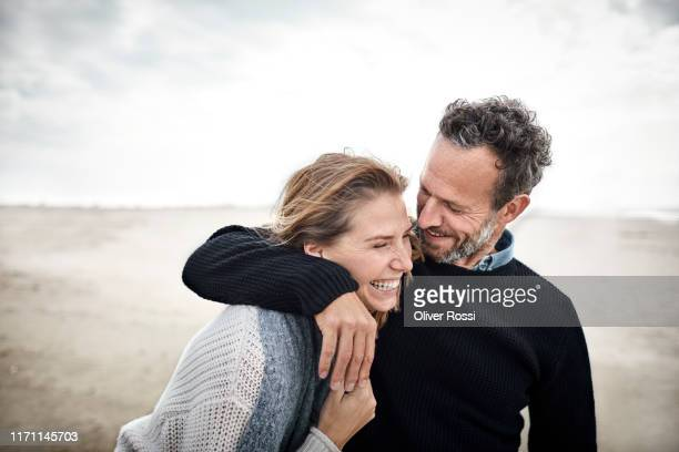 happy couple hugging on the beach - mid volwassen stockfoto's en -beelden