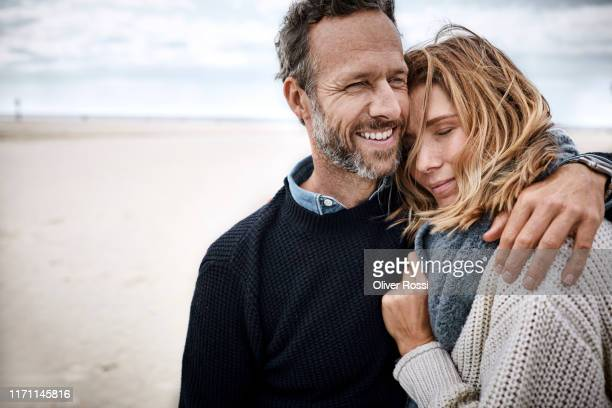 happy couple hugging on the beach - adulte d'âge moyen photos et images de collection