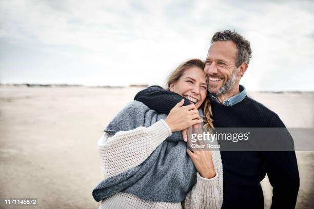 happy couple hugging on the beach - heteroseksueel koppel stockfoto's en -beelden