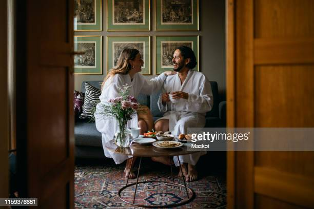 happy couple in bathrobes in hotel room - hotel stock-fotos und bilder