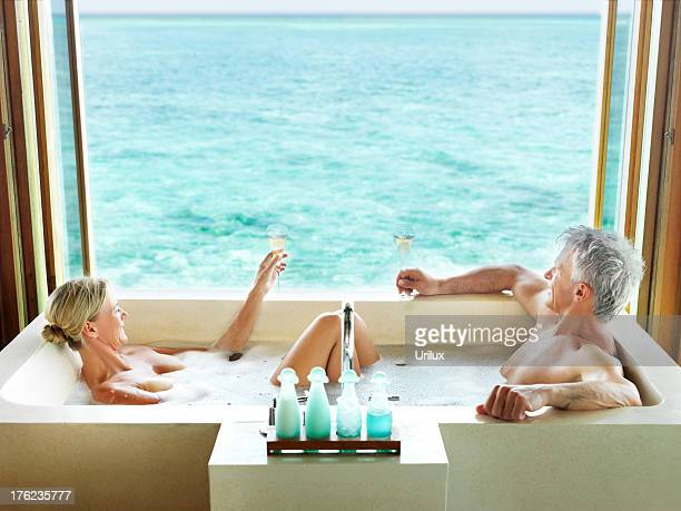 happy couple in bathtub enjoying a glass of drink - couple bathtub stock pictures, royalty-free photos & images
