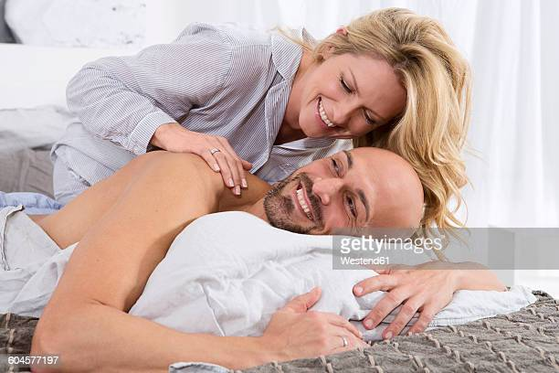 Happy couple in bedroom, woman giving man a back massage