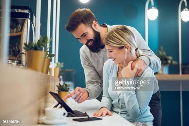 Couple heureux à café avec tablette numérique et surfer sur le web