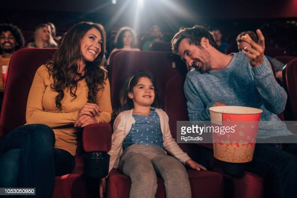 Happy couple in cinema with a daughter