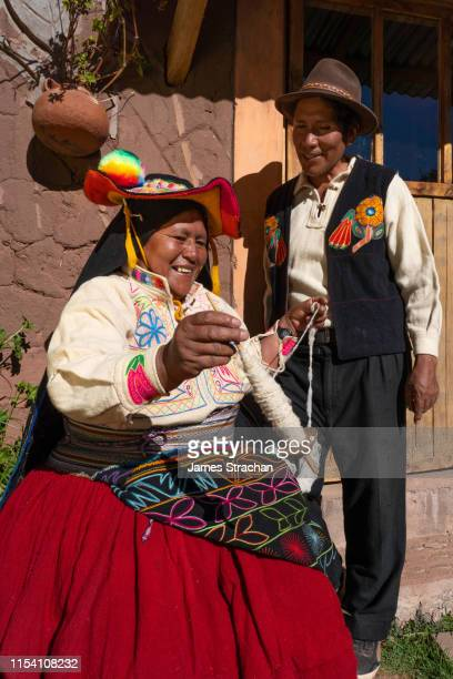 happy couple in colourful local traditional dress talking and laughing as wife spins wool outside their house, llachon island, lake titicaca (2 model releases) - indigenous culture stock pictures, royalty-free photos & images