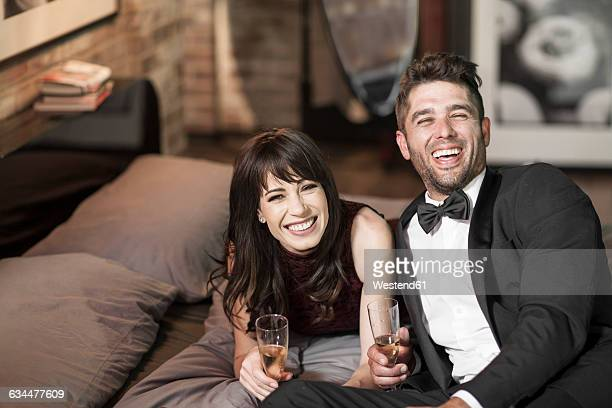 Happy couple in elegant clothing drinking champagne in bed