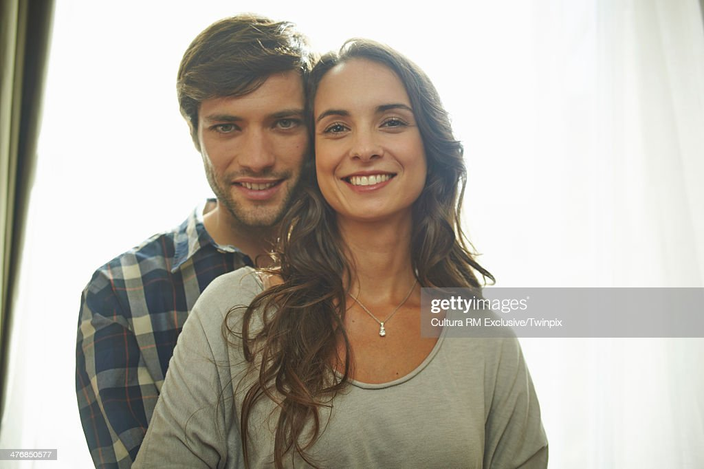 Happy couple in front of apartment window : Stock Photo