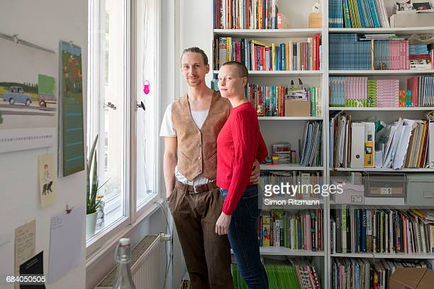 Happy couple in front of bookshelf at home