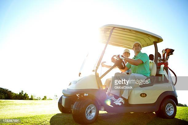 Happy couple in golf cart about to play some holes