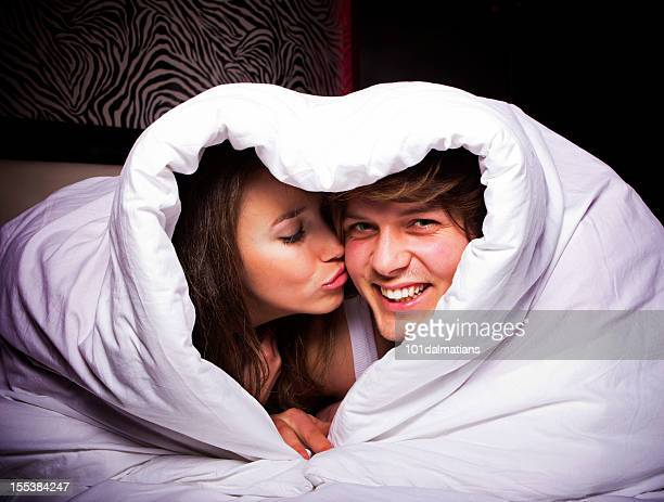 happy couple in heart shaped blanket - good morning kiss images stock photos and pictures
