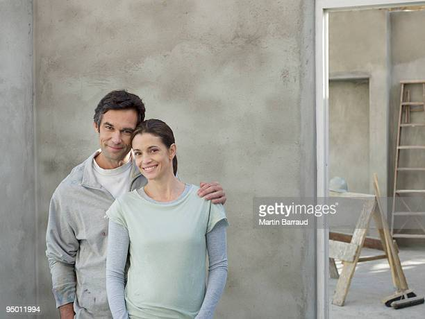 Happy couple in house under construction
