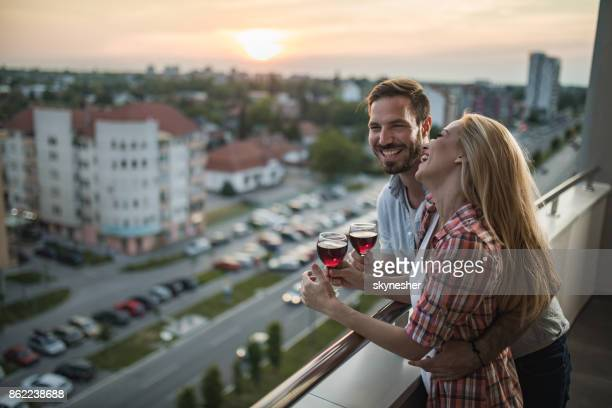 Happy couple in love enjoying in glass of wine on a penthouse balcony at sunset.