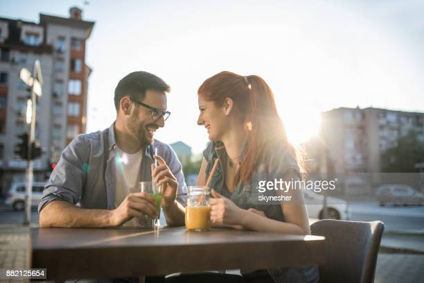 Happy couple in love talking to each other in a street cafe.