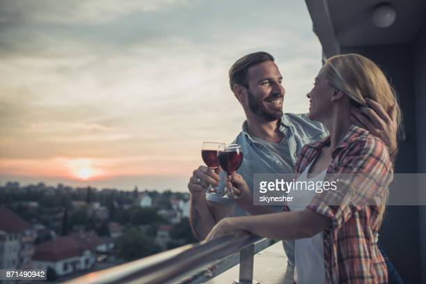 happy couple in love toasting with wine and communicating on a penthouse balcony at sunset. - adults only stock pictures, royalty-free photos & images